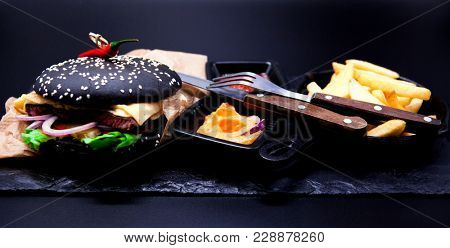 Delicious set: burger, French fries, curry sauce, chilli sauce, fork and knife.