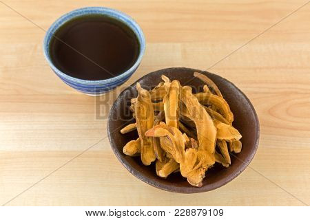 Bowl of herbal sliced dried Lingzhi mushroom next to hot Reishi tea. It is medicinal mushroom in traditional Chinese medicine