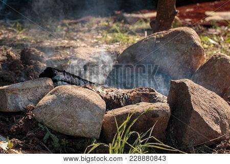 Embers On Ground With Stone: Charcoal And Ashes After Cooking.