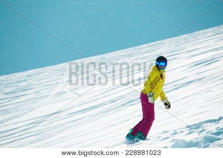 Photo of sports woman wearing ahelmet and mask, snowboarding from mountain slope