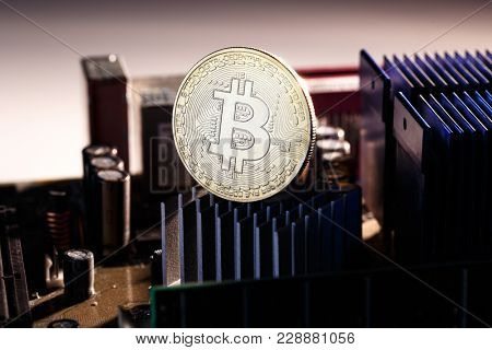 Photo of bitcoin and processor on orange background