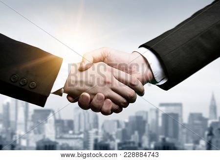 Business handshake and business people on city background vintage tone