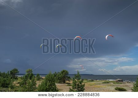 A kite surfer rides on the sea. Kites in the sky. Kite Boarding, extreme sport on Mohni, small islan