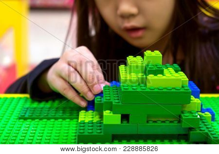 Bangkok, Thailand - February 11, 2018 - Imaginative Child Builds With Green And Blue Lego Bricks