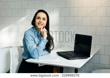 The Girl Is Sitting At The Table In The Office Smiling Behind The Laptop