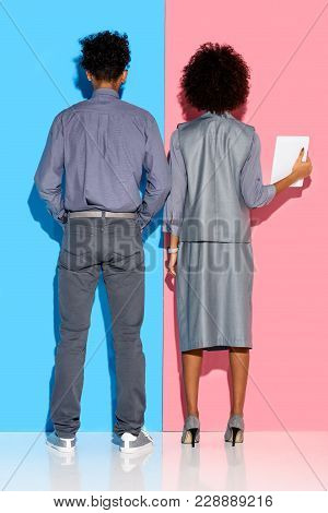Rear View Of Young African Amercian Businessman Standing By Businesswoman  With Tablet In Hands On P