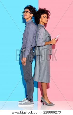 Young African Amercian Businessman Standing By Businesswoman With Tablet In Hands On Pink And Blue B
