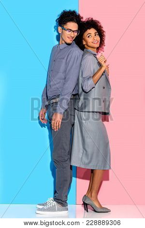 Young African Amercian Smiling Couple In Grey Suits Standing Back To Back On Pink And Blue Backgroun