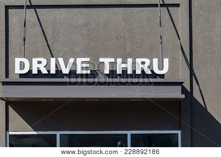 A Drive Thru Window With White Letters Sign On Gray Building.