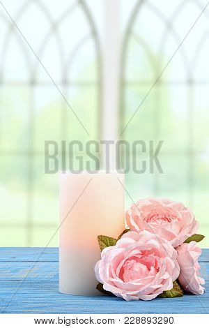 Candle With Pink Roses On Blue Wood Table