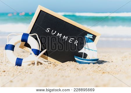 Closeup Of A Chalkboard With The Text Summer Written On The Sand Of A Beach. Summer Concept
