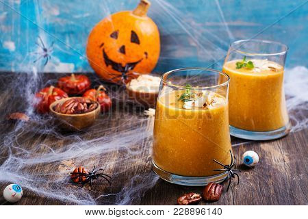 Pumpkin Smoothie With Coconut Chips, Cinnamon And Mint. Halloween Party Treat On Spooky Background.