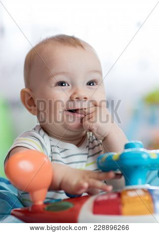 Portrait Of Adorable Baby Boy With Finger In His Mouth