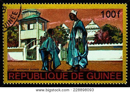 Moscow, Russia - February 28, 2018: A Stamp Printed In Guinea Shows Man And Little Boy In Traditiona