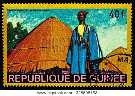 Moscow, Russia - February 27, 2018: A Stamp Printed In Guinea Shows Man In Traditional Clothes In Af