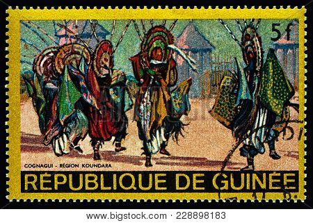 Moscow, Russia - February 27, 2018: A Stamp Printed In Guinea Shows Traditional Dance In African Vil