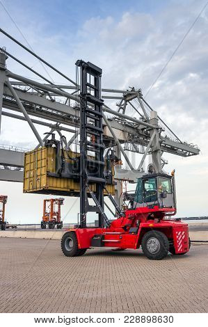Mobile Cargo Container Handler In Action At A Shipping Container Terminal In A Port.