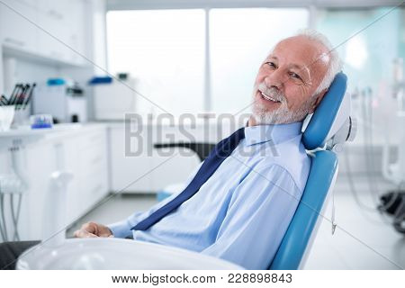Elderly Man In Dentist's Chair Without Fear Waiting For Treatment
