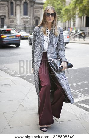 London, England - September 15, 2017 Beautiful And Stylish Girl In A Gray Checkered Coat And Burgund