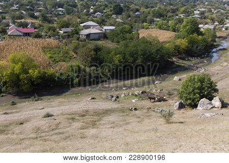 View On The Village. River Near A Village And Stonefield.