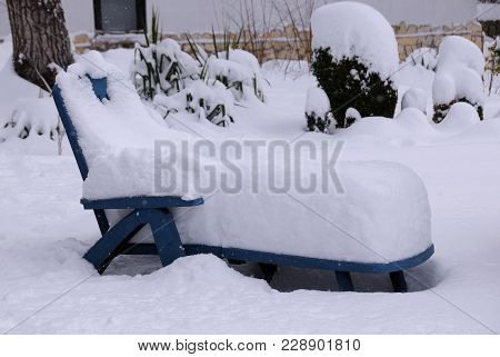 Sunbed Coverd With Snow In The Garden.