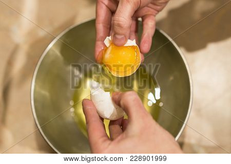 Female Hands With An Open Chicken Egg.