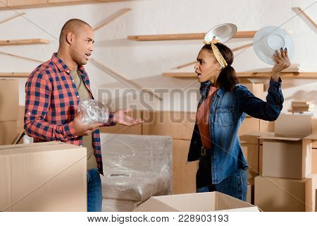 African American Couple Unpacking And Quarreling In New Apartment With Cardboard Boxes