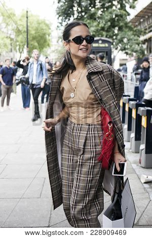 London, England - September 15, 2017 Girl With Her Hair Tucked Into Her Tail In A Classic Checkered