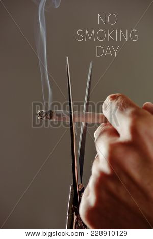 closeup of a young caucasian man cutting a lit cigarette with scissors and the text no smoking day