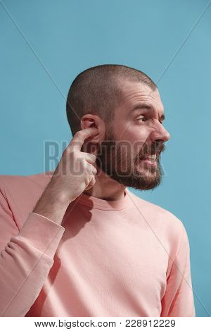 Sore Ear. Ear Ache Concept. The Sad Crying Man With Headache Or Pain On Trendy Blue Studio Backgroun