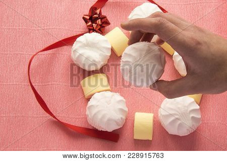 Hand Hold White Zephyr With Colorful Marshmellows In Background. Yummy Sweets Desserts Wallpaper.