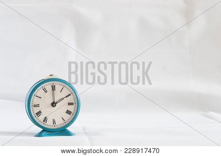 vintage alarm clock with roman numeral on a white background.