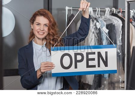 Happy Young Dry Cleaning Manageress Holding Open Sign