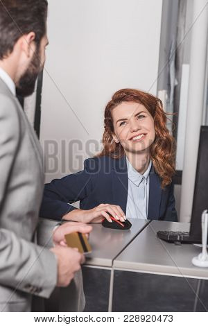 Handsome Man Holding Credit Card At Cashier Workplace