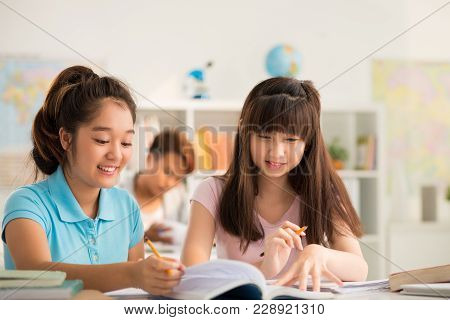 Cheerful Asian Students With Toothy Smiles Sitting At Desk And Doing Exercise Together While Having