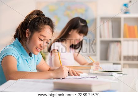 Profile View Of Pretty Teenage Student Sitting At Desk And Writing Essay With Enthusiasm, Interior O
