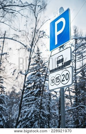 A Closeup Of A Toll Road Street Sign On The Background Of Winter Trees