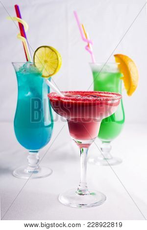 Three Colorful Cocktails In Glass With Fruits Slice On White Background