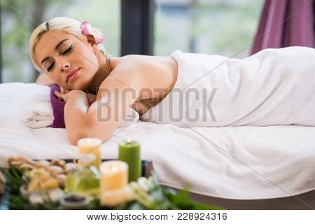Profile View Of Attractive Young Woman Lying On Massage Table With Eyes Closed While Spending Weeken