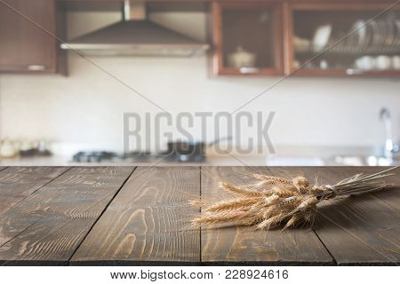 Blurred Background. Modern Defocused Kitchen With Wheat On Old Wooden Board.