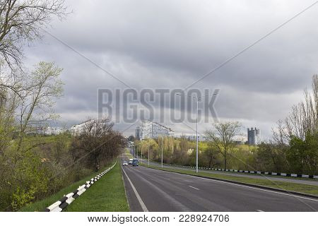 Main Road To The City. View Of A City With Dark Clouds.