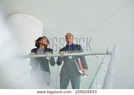 Low Angle View Of Cheerful African American Managers Standing At Spacious Office Lobby And Chatting
