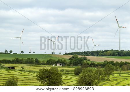 Wind Turbine Renewable Energy Source Summer Landscape With Clear Blue Sky And Field In The Foregroun