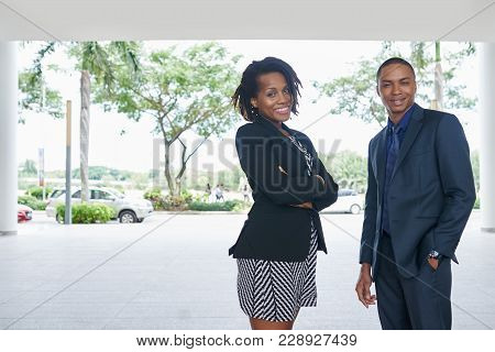 Attractive Young White Collar Worker And Her Handsome Coworker Looking At Camera With Toothy Smiles