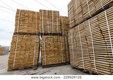 Stack Of New Wooden Boards And Studs At The Lumber Yard. Wooden Plates On Piles For Furniture Materi