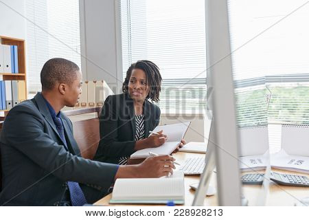Pretty African American Manager And Her Young Colleague Gathered Together In Modern Boardroom And Ha