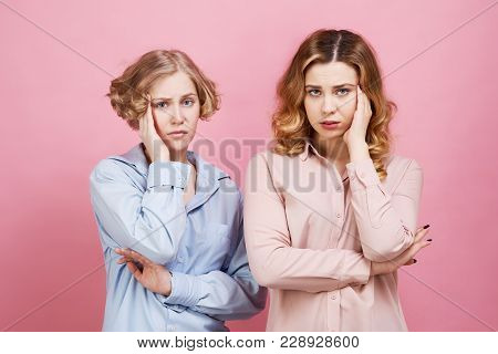 Two Young Women Are Upset And Holding Onto Their Heads. Headache And Anxiety Spoil Their Mood, They