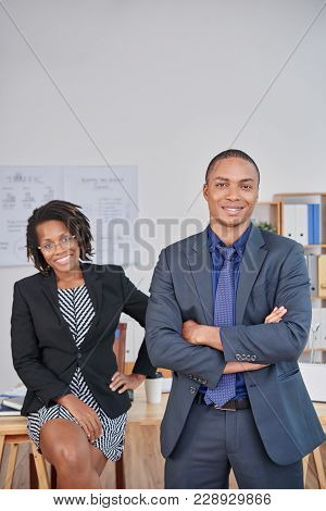 Group Portrait Of Confident Young White Collar Workers Looking At Camera With Wide Smiles While Havi