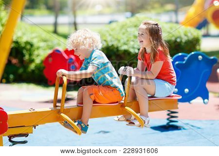 Kids On Playground. Children Play In Summer Park.