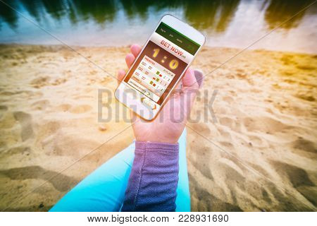 Betting on sports, hand holding smart phone with working online betting mobile application as a concept of gambling addiction poster